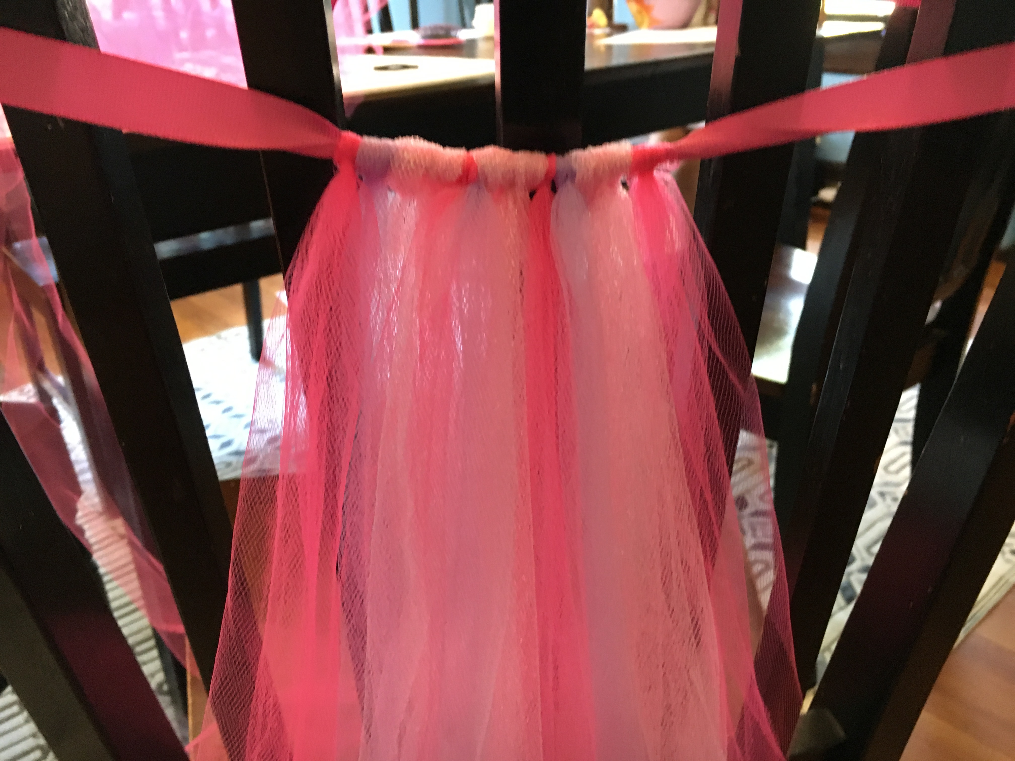 When making the DIY No Sew Tulle Tutu I found it easiest to tie the ribbon around the back of a chair to attach the tulle. That way I could quickly tie the loops while also ensuring that the length was somewhat uniform.